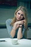 A jovem mulher espera pelo telefone em uma cozinha da noite Imagens de Stock