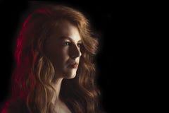 Jovem mulher esplêndida na obscuridade Espaço para o texto Fotografia de Stock