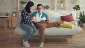A jovem mulher está ajudando um homem com um braço e um pé quebrados video estoque