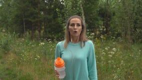A jovem mulher está andando com o cão na floresta video estoque