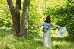 A jovem mulher está andando em um parque no chapéu e em uma saia longa com a foto de stock