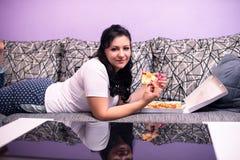 A jovem mulher está apreciando a pizza em um sofá Imagens de Stock