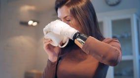 A jovem mulher está bebendo de um copo com seu braço robótico vídeos de arquivo