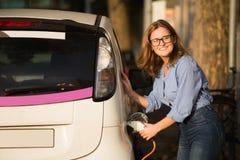 A jovem mulher está carregando um carro bonde imagem de stock