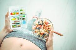 A jovem mulher está comendo uma salada de fruto e está usando uma aptidão app em seu smartphone após um exercício Foto de Stock