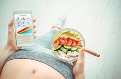 A jovem mulher está comendo uma salada e está usando uma aptidão app em seu smartphone após um exercício Fotografia de Stock Royalty Free