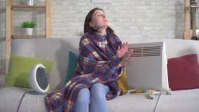 A jovem mulher está congelando-se em seu apartamento na sala de visitas vídeos de arquivo