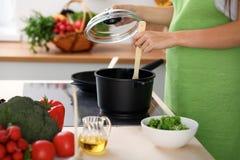A jovem mulher está cozinhando pelo fogão na cozinha, fim acima foto de stock royalty free