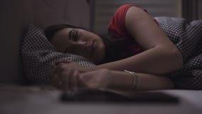 A jovem mulher está dormindo em uma cama confortável e então acorda e começa-o usar seu dispositivo móvel filme