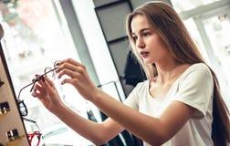 A jovem mulher está escolhendo uns vidros na loja do ótico fotos de stock