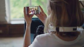 A jovem mulher está falando aos amigos em linha com o smartphone que olha a tela e que fala o assento no sofá em moderno video estoque