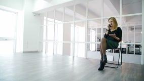 A jovem mulher está falando no telefone ao sentar-se no escritório moderno filme