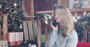A jovem mulher está falando no telefone celular no fundo da decoração do Natal vídeos de arquivo