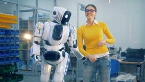 A jovem mulher está golpeando a humano-como o robô depois que a espanca playfully