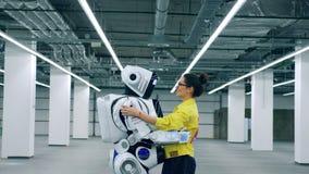 A jovem mulher está guardando um cyborg e está falando-lhe vídeos de arquivo