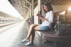 A jovem mulher está lendo em seu diário imagens de stock