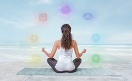 A jovem mulher está meditando sobre a praia com os chakras que incandescem em torno dela fotos de stock royalty free