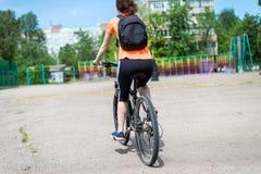 A jovem mulher está montando uma bicicleta, vista traseira fotografia de stock royalty free