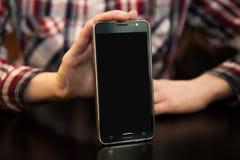 A jovem mulher está mostrando um smartphone na tabela Imagem de Stock