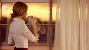 A jovem mulher está na frente da janela e bebe um copo do chá ou do café filme