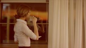 A jovem mulher está na frente da janela e bebe um copo do chá ou do café vídeos de arquivo