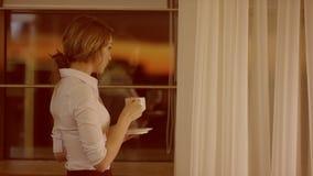 A jovem mulher está na frente da janela e bebe um copo do chá ou do café video estoque