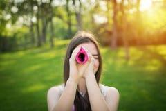 A jovem mulher está olhando através de um tabela-pano rolado Fotografia de Stock Royalty Free