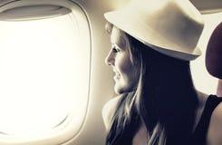 A jovem mulher está olhando através de uma janela no avião imagem de stock royalty free