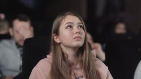 A jovem mulher está olhando o filme no cinema emoção - interesse video estoque
