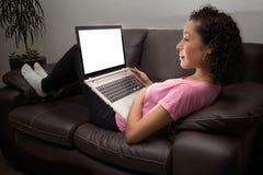 A jovem mulher está olhando o filme no portátil em casa fotografia de stock