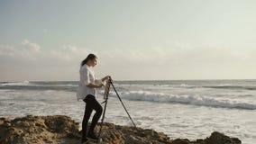 A jovem mulher está pintando na armação no banco do mar filme