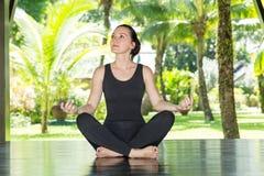 A jovem mulher está praticando a ioga e os pilates na natureza Fotos de Stock Royalty Free