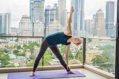 A jovem mulher está praticando a ioga na manhã em sua sagacidade do balcão imagens de stock royalty free