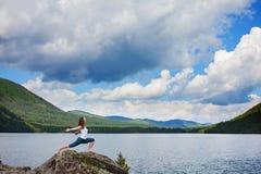 A jovem mulher está praticando a ioga no rio da montanha fotos de stock
