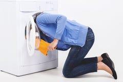 A jovem mulher está procurando a roupa no cilindro da máquina de lavar fotografia de stock royalty free
