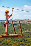 A jovem mulher está pronta para descer no zipline na montanha, esporte extremo Imagem de Stock