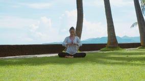 A jovem mulher está relaxando praticando a ioga na pose dos lótus na praia do oceano na ilha Bali, no fundo bonito e nos sons da  vídeos de arquivo