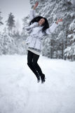 A jovem mulher está saltando na floresta do inverno Fotografia de Stock