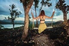 A jovem mulher está sentando-se em um balanço Imagem de Stock Royalty Free
