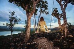 A jovem mulher está sentando-se em um balanço Fotografia de Stock