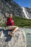 A jovem mulher está sentando-se na pedra, Briksdalsbreen, Noruega Fotografia de Stock