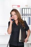 A jovem mulher está telefonando no escritório Imagem de Stock Royalty Free