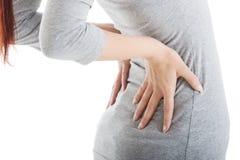 A jovem mulher está tendo a dor nas costas. Foto de Stock