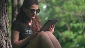 A jovem mulher está usando a tabuleta digital no parque video estoque