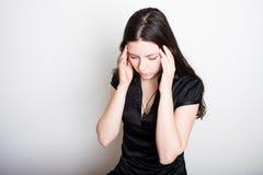 A jovem mulher est? sofrendo de uma dor de cabe?a Retrato de uma menina que embreia sua cabe?a Enxaqueca e problemas da press?o s foto de stock