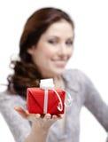 A jovem mulher estica para fora um presente Fotos de Stock