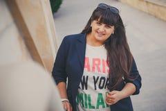 Jovem mulher excesso de peso bonita de sorriso feliz na obscuridade - casaco azul fora na rua Jovem mulher gorda segura Mulher de Foto de Stock