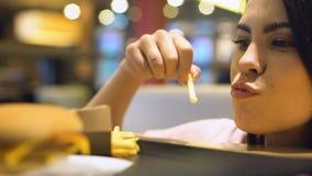 Jovem mulher excitada que come batatas fritadas francesas, prazer da comida lixo, refeição filme