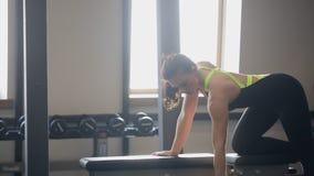 A jovem mulher exercita com peso no clube de aptidão video estoque