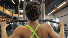 A jovem mulher exercita usando a máquina do treinamento no gym Vista da parte traseira video estoque